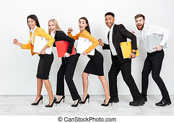 Happy colleagues walking isolated with folders in office
