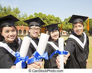 happy college graduate show diplomas at ceremony