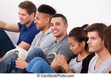 Happy College Student Sitting With Classmates - Portrait of...