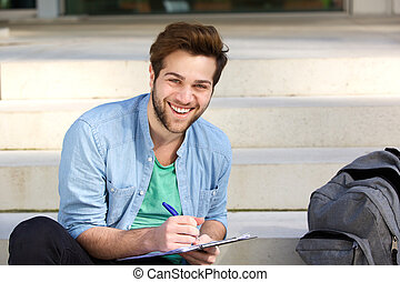 Happy college student writing on notepad outside