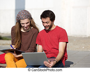 Happy college students sitting outdoors and working on laptop