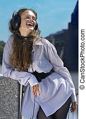 happy collegian - Happy girl is listening music on the quay...