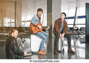 Happy comrades having fun in airport hall