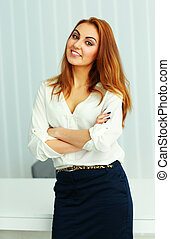 Happy confident businesswoman with arms folded standing in office