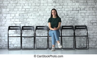 Happy confident female job applicant looking at camera sit alone on chairs, smiling millennial business woman graduate professional waiting for employment interview, leadership and recruit concept