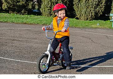 Happy confident little boy on his bike