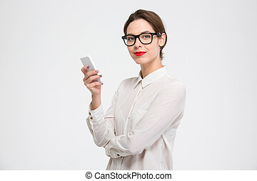 Happy confident young business woman in glasses using smartphone