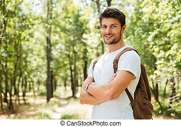 Happy confident young man standing with arms crossed in forest