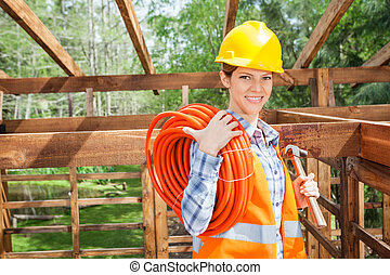 Happy Construction Worker Holding Pipe And Hammer At Site