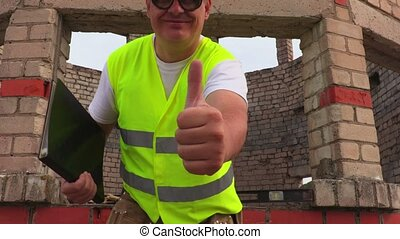 Happy construction worker shows thumb up