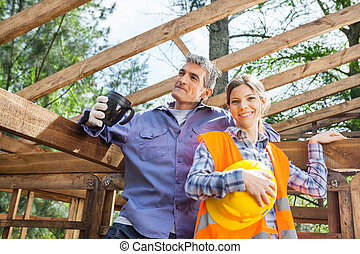 Happy Construction Worker Standing With Colleague Holding Coffee
