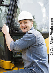 Happy construction worker - A happy smiling builder sitting...