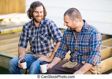 Happy construction workers holding disposable coffee cups while sitting on wooden frame at construction site