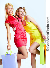 Happy consumers - Young females with shopping bags over...
