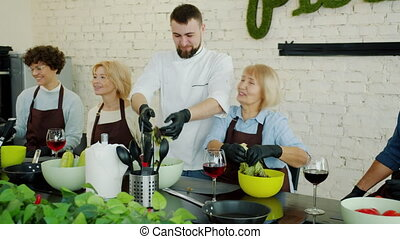 Happy cookery teacher making salad while cheerful women in ...