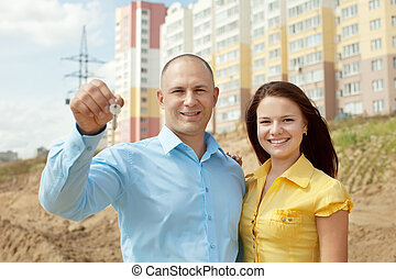 Happy couple against building new house