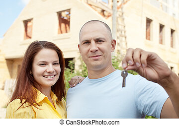 Happy couple against building new house - Happy couple with...