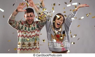 happy couple at christmas party under confetti -...