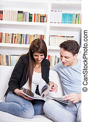 happy couple at home reading newspapers in front of library