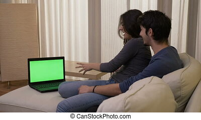Happy couple at home watching a comedy movie on a laptop with green screen laughing and having a good time