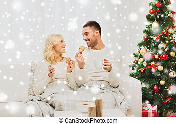 happy couple at home with christmas tree