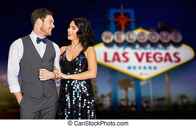 happy couple at party over las vegas sign at night