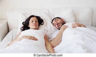 happy couple awakening in bed at home - people, rest,...