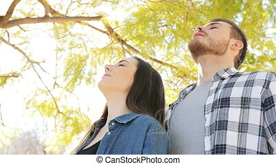 Happy couple breathing fresh air in a park - Portrait of a...