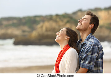 Happy couple breathing fresh air together on the beach