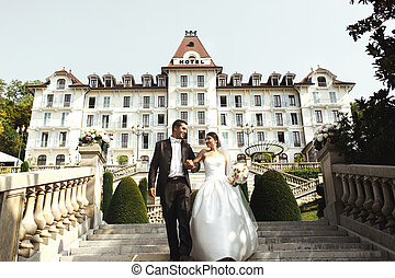 Happy couple bride and groom walking on stairs in front of luxury hotel