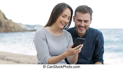 Happy couple browsing phone on the beach