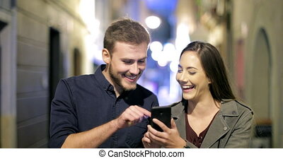 Happy couple browsing phone walking in the night