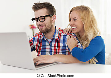 Happy couple browsing something on laptop