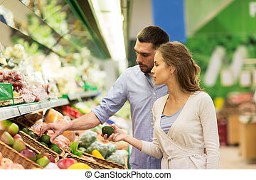 happy couple buying avocado at grocery store