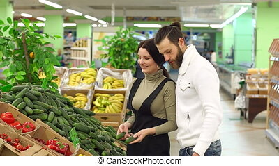 Happy couple buying cucumbers at grocery store or supermarket.