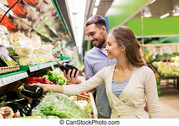 happy couple buying eggplant at grocery store
