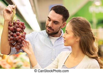 happy couple buying grapes at grocery store