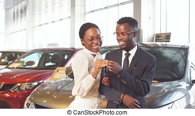 Happy couple buying new car in showroom. - Happy couple...
