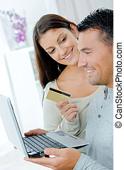 happy couple buying on line with a credit card