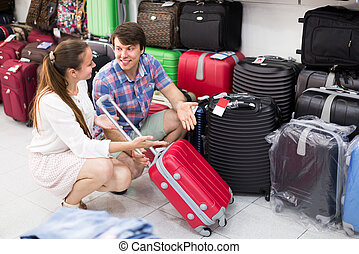 Happy couple buying red suitcase