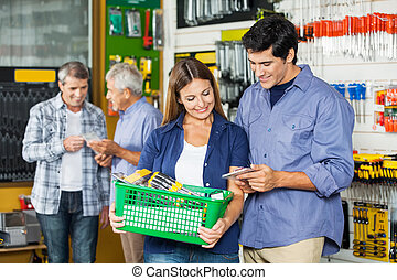 Happy Couple Buying Tools At Hardware Store - Happy couple...