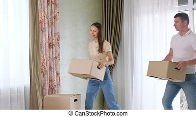 happy couple carries boxes with old things into new house