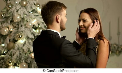 Happy couple celebrating New Year Eve together, woman wearing gold dress, man stylish suit.