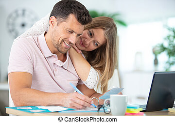 happy couple checking accountancy at home