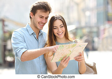 Happy couple checking paper map on vacation