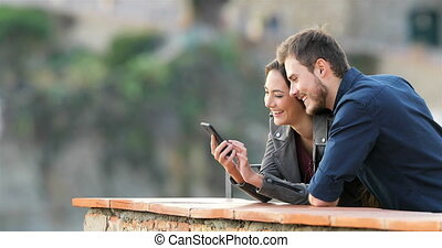 Happy couple checking phone content in a balcony