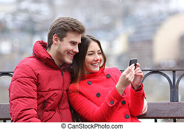 Happy couple checking phone on winter holiday