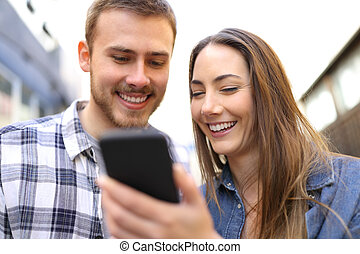 Happy couple checking phone online content in the street