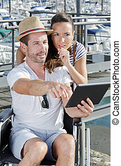 happy couple checking something at the tablet