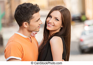 Happy couple. Cheerful young loving couple standing close to each other while woman looking at camera and smiling